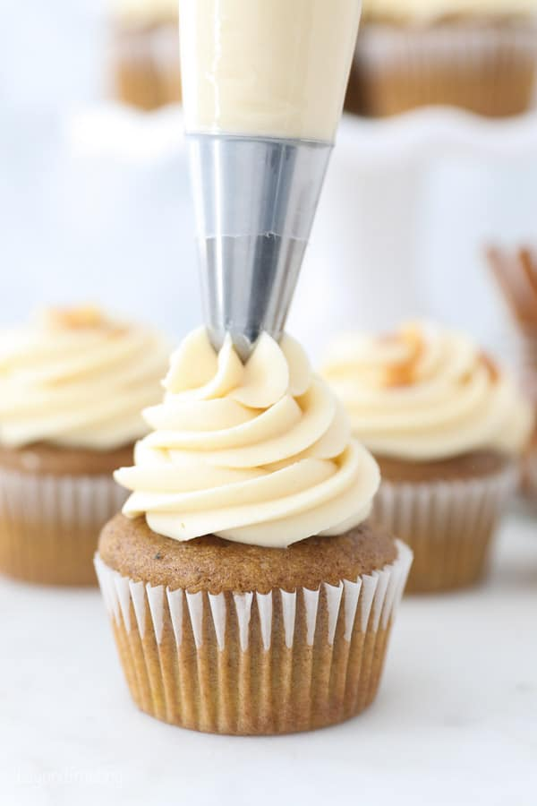 A piping bag piping frosting onto a cupcake