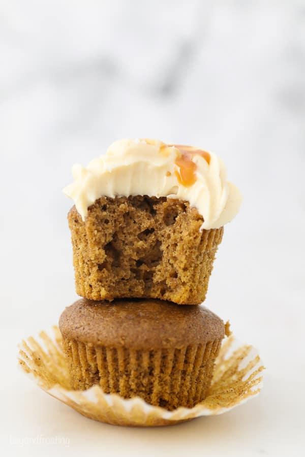 Two stacked pumpkin cupcakes, the top one has a bite missing
