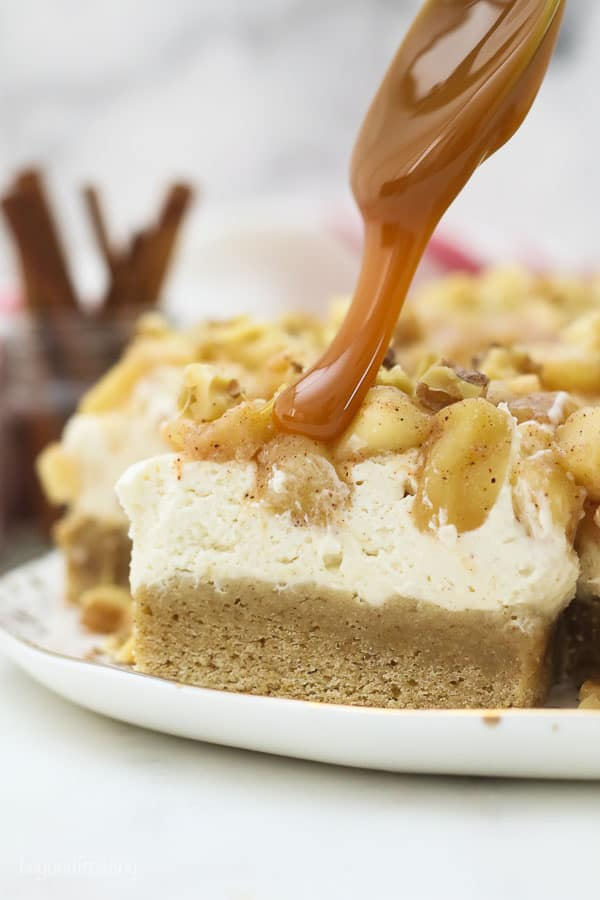 caramel dripping over apple filling on top of a cheesecake bar