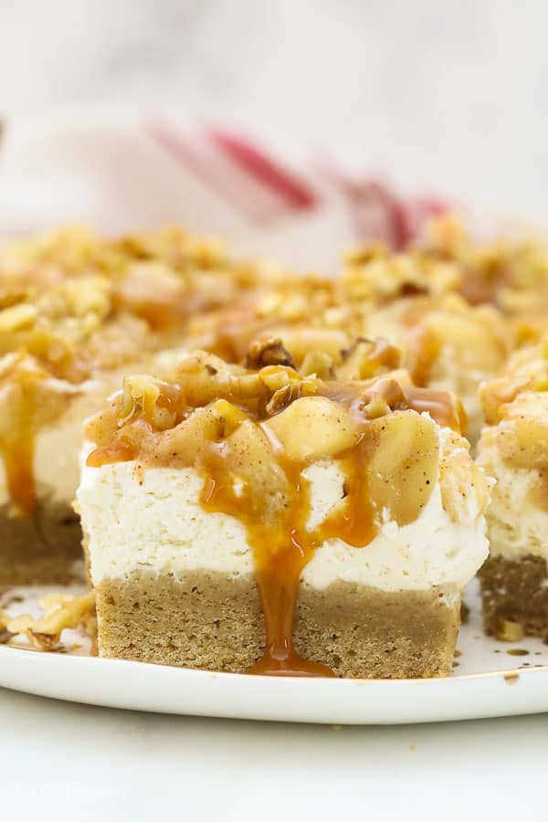 Apple cheesecake bars on a plate with dripping caramel