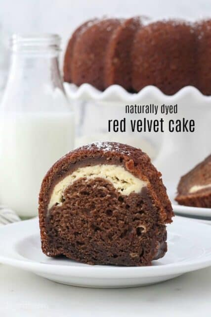 A slice of red velvet bundt cake, with a cake stand in the background and a text overlay