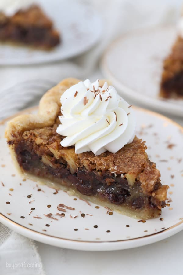 An overhead shot of a slice of walnut pie with whipped cream on top