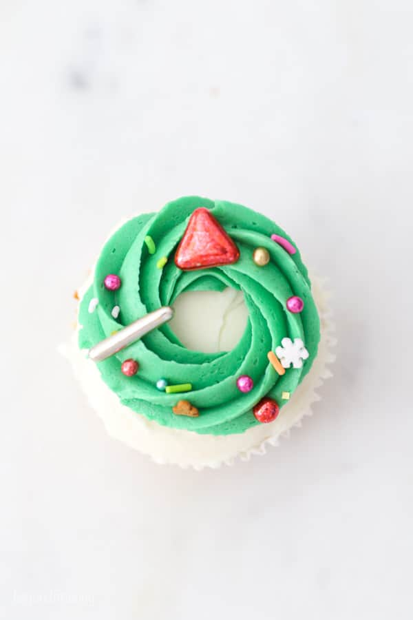top down view of a cupcake decorated with a Christmas wreath and sprinkled