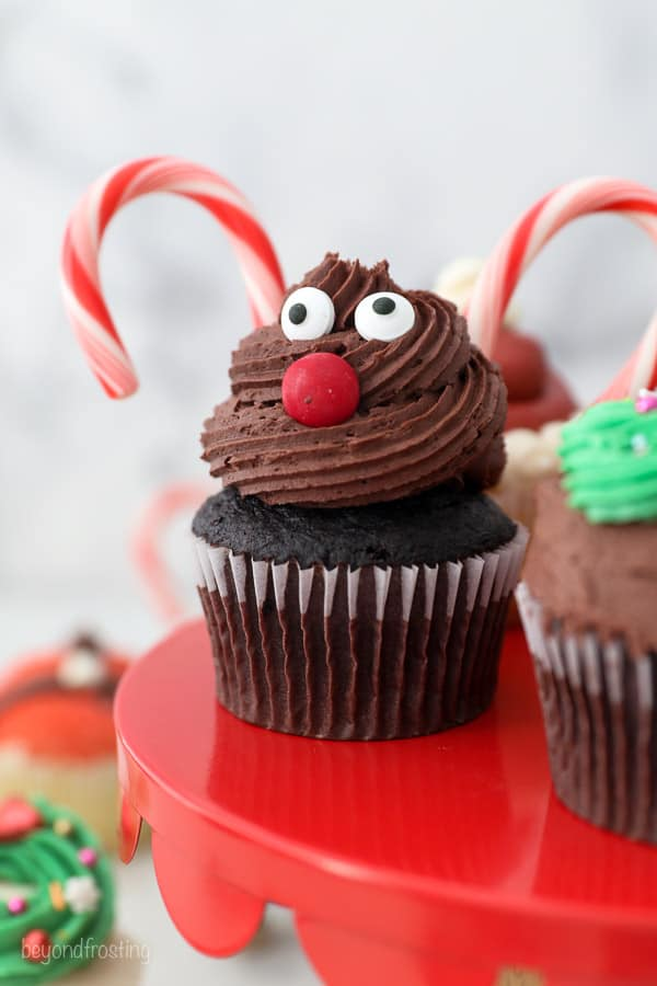 A reindeer cupcake on a red cake stand