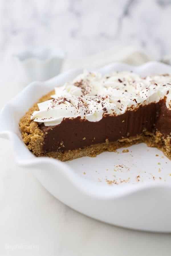 a sliced chocolate pudding pie in a white pie plate