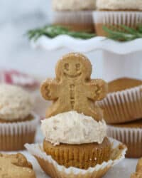 A gingerbread man on top of a frosted cupcake