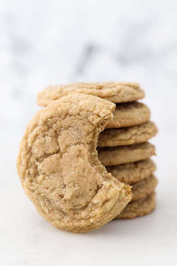 A cookie with a bite taken out of it leaning up against a stack of cookies