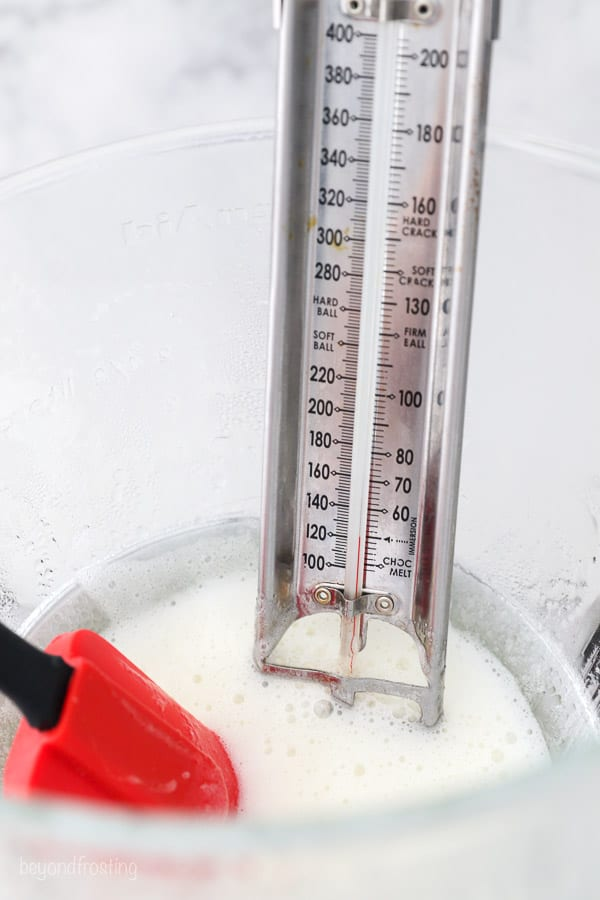A candy thermometer attached to a glass mixing bowl