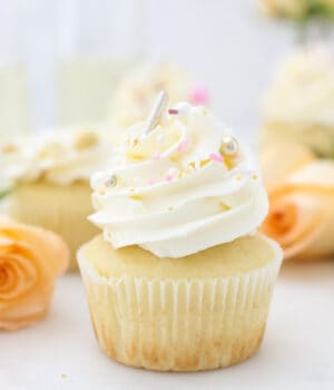 A gorgeous champagne cupcake with frosting and sprinkles and roses in the background