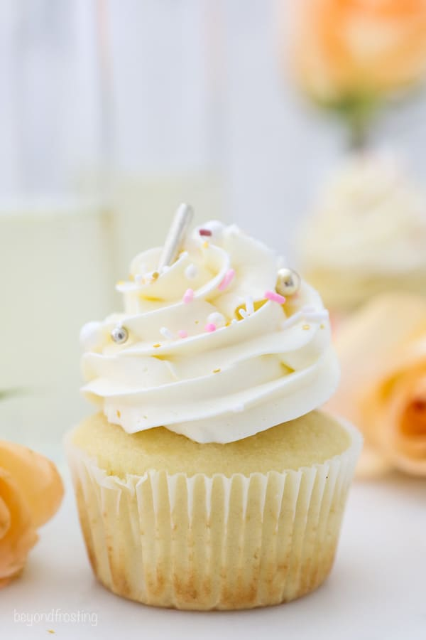 A gorgeous champagne cupcake with frosting and sprinkles