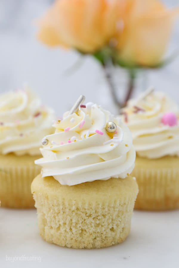 three frosted cupcakes with gold, white and pink sprinkles