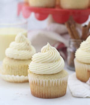 three eggnog cupcakes and a red cake stand in the background