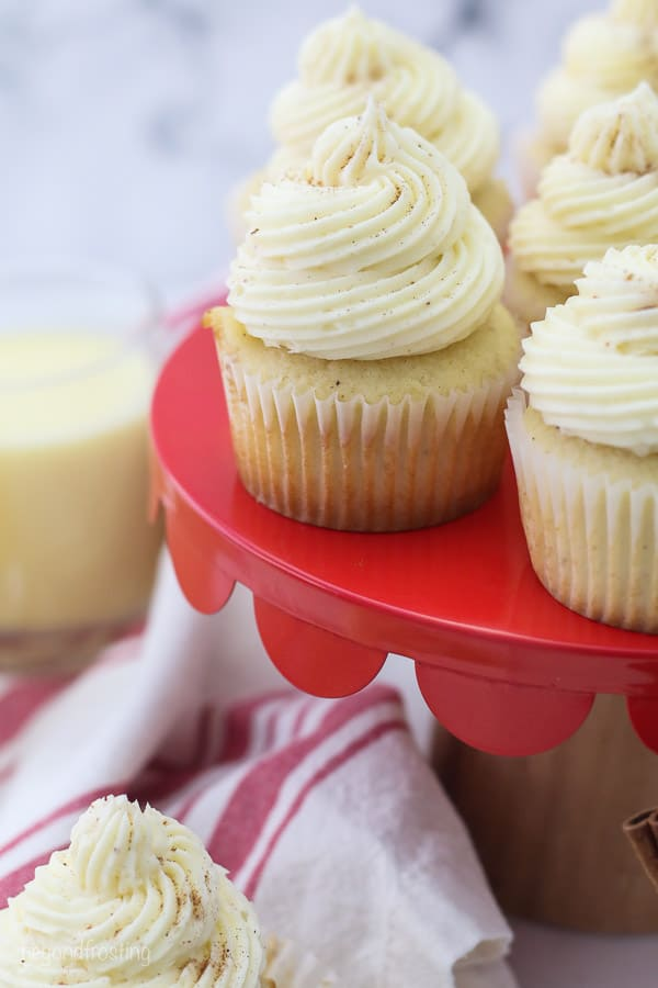a red cake stand with eggnog cupcakes