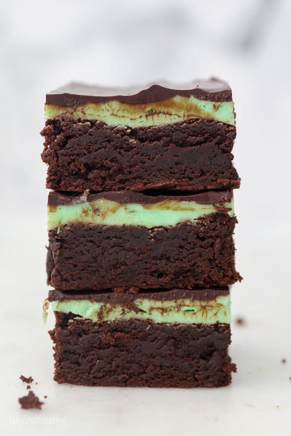 A stack of 3 brownies with mint frosting