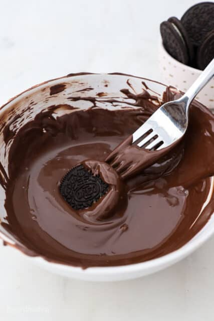 A Bowl of Melted Chocolate with an Oreo and a fork dipping in it