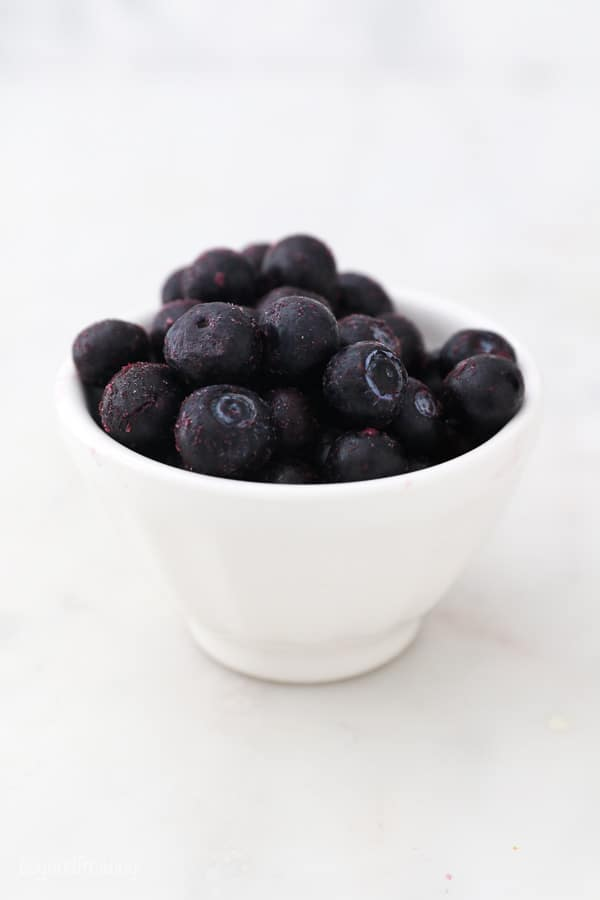 a small white bowl with frozen blueberries
