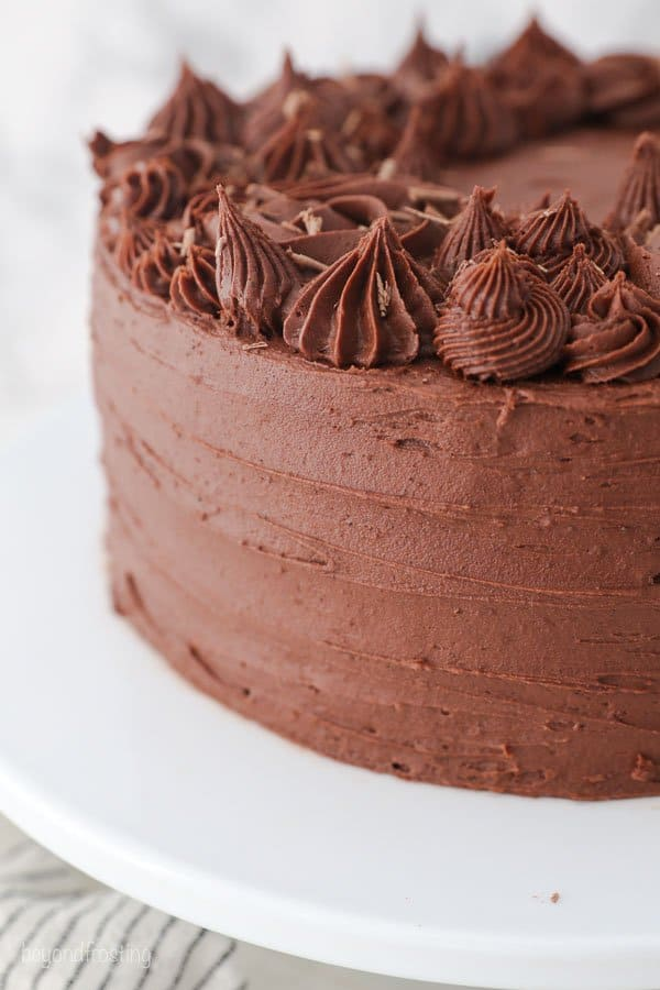 A close up of the side of a chocolate frosted cake showing the decorations