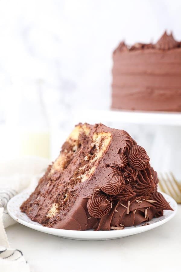 a close up of a chocolate frosted cake with rosettes