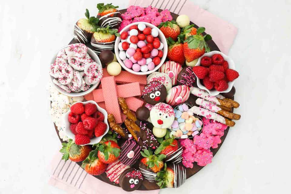 Overhead shot of a dessert charcuterie board for Valentine's day with candy, fruit and cookies and pink towel