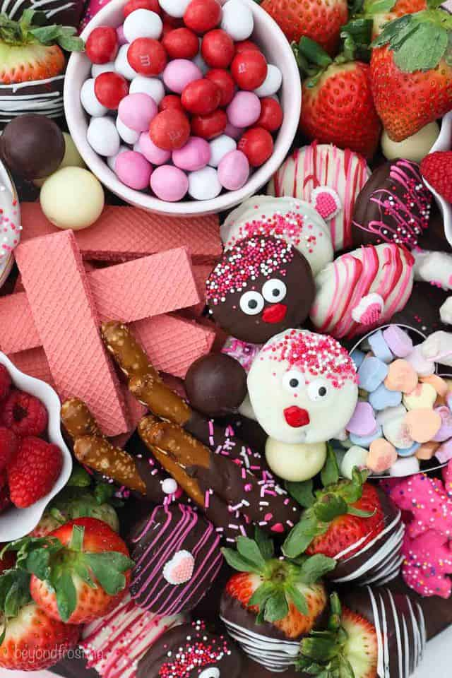 overhead shot of various cookies, candies and chocolate covered treats on a Valentine's day dessert board