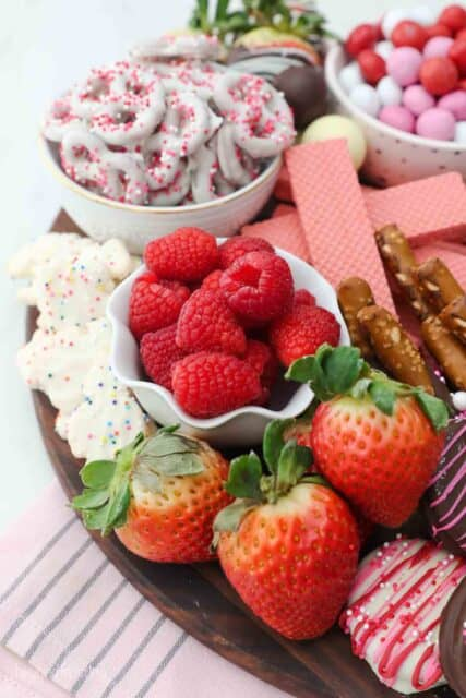 strawberry, raspberries and white chocolate covered pretzels on a dessert board
