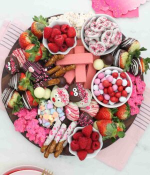 Overhead shot of a dessert charcuterie board for Valentine's day with candy, fruit and cookies
