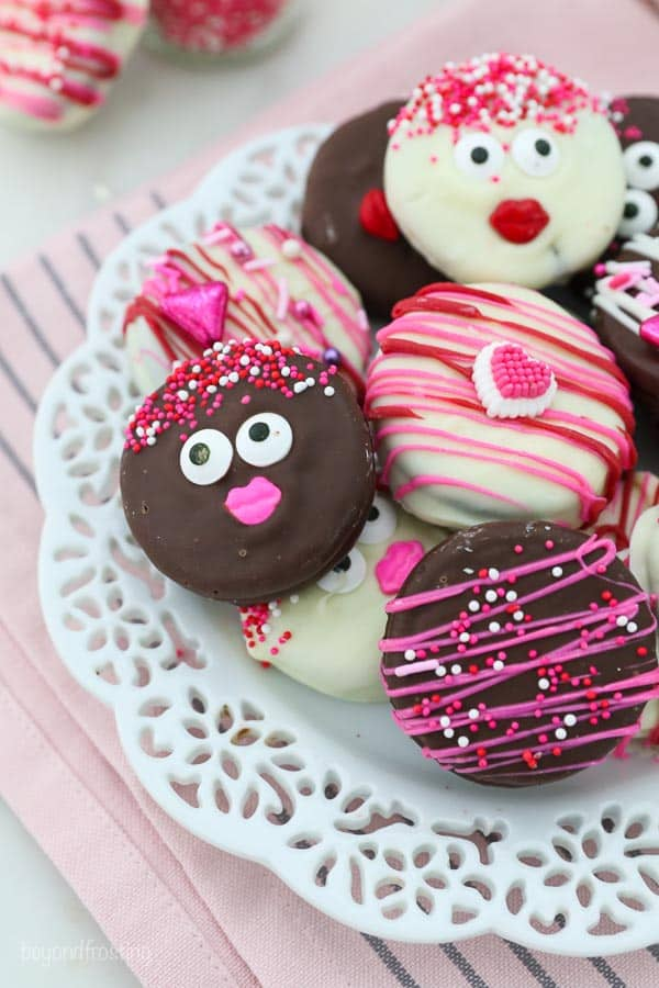 a plate of chocolate covered Oreos with Valentine's Day sprinkles, icing decorations and pink chocolate drizzle