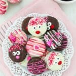a plate of Chocolate dipped Oreos decorated for Valentine's Day on a white plate and pink napkin