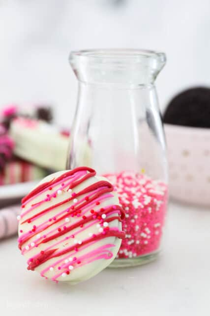 A white chocolate dipped Oreo with pink and red drizzle and red, white and pink sprinkles