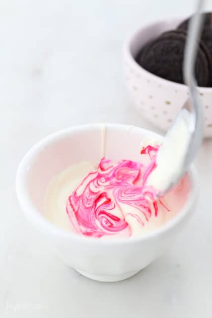 a small white dish with melted white chocolate, and pink food coloring being stirred with a spoon