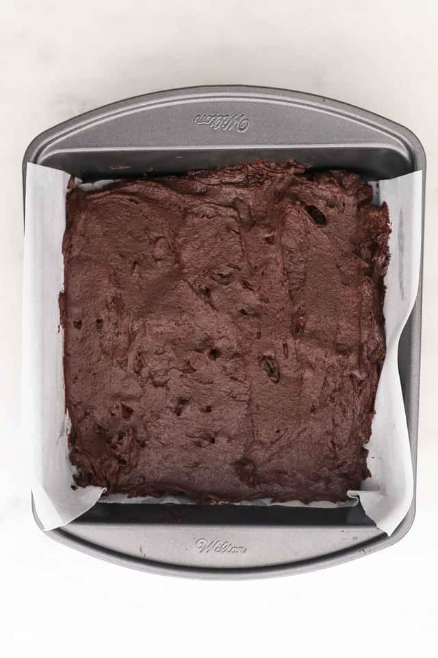 overhead shot of brownie batter in an metal pan lined with parchment paper
