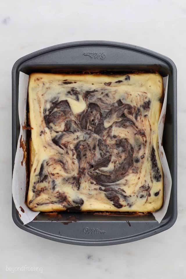 overhead shot of Baked cheesecake brownies in a metal pan