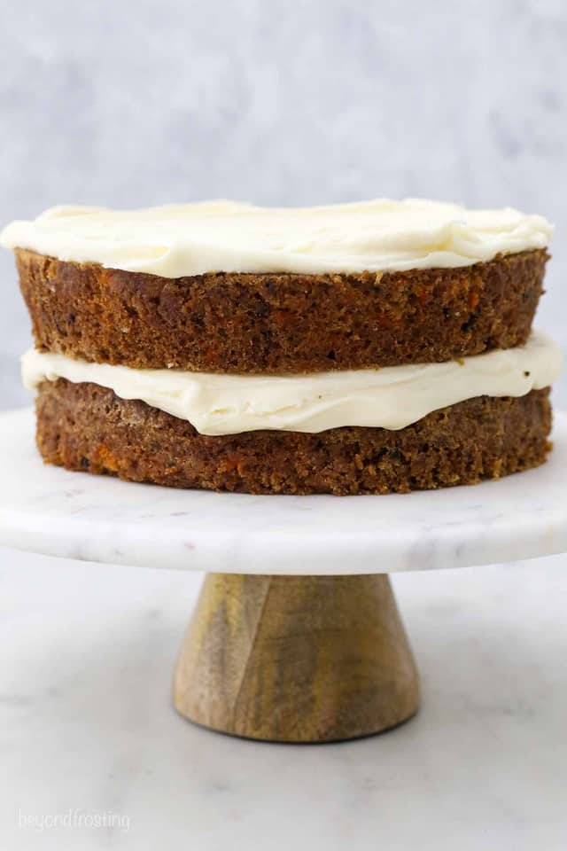 a marble cake plate with two layers of carrot cake and cream cheese frosting