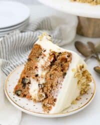 A slice of carrot cake on a gold polka dot plate