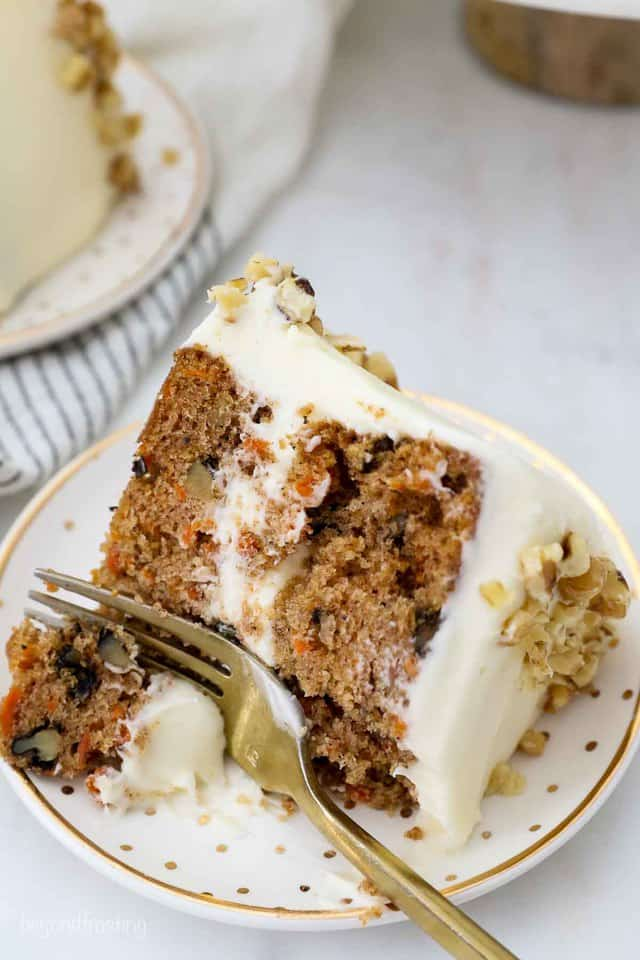 A slice of carrot cake with a couple bites removed and a gold fork