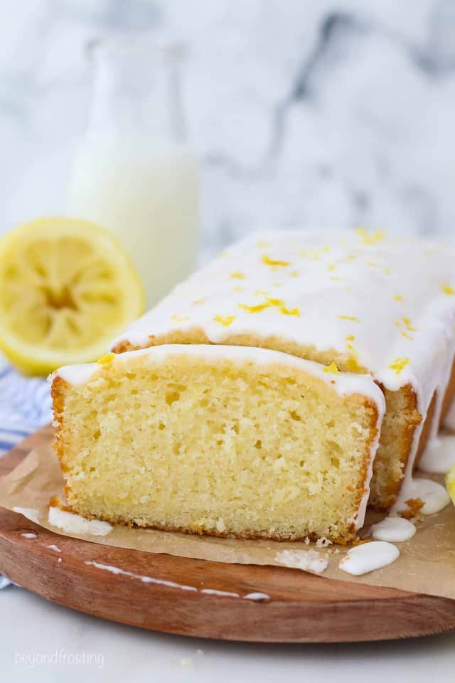 A sliced Lemon loaf dripping with glaze on a piece of parchment paper