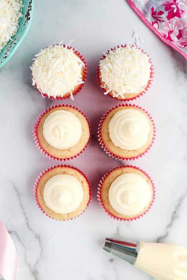 overhead shot of 6 frosted cupcakes and two garnished with coconut