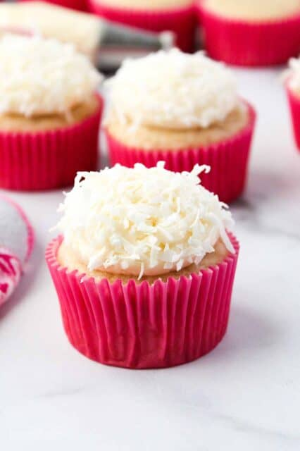 Shredded coconut on top of a frosted cupcake in a pink wrapper