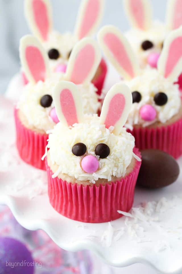 a white cake stand with bunny cupcakes and chocolate eggs