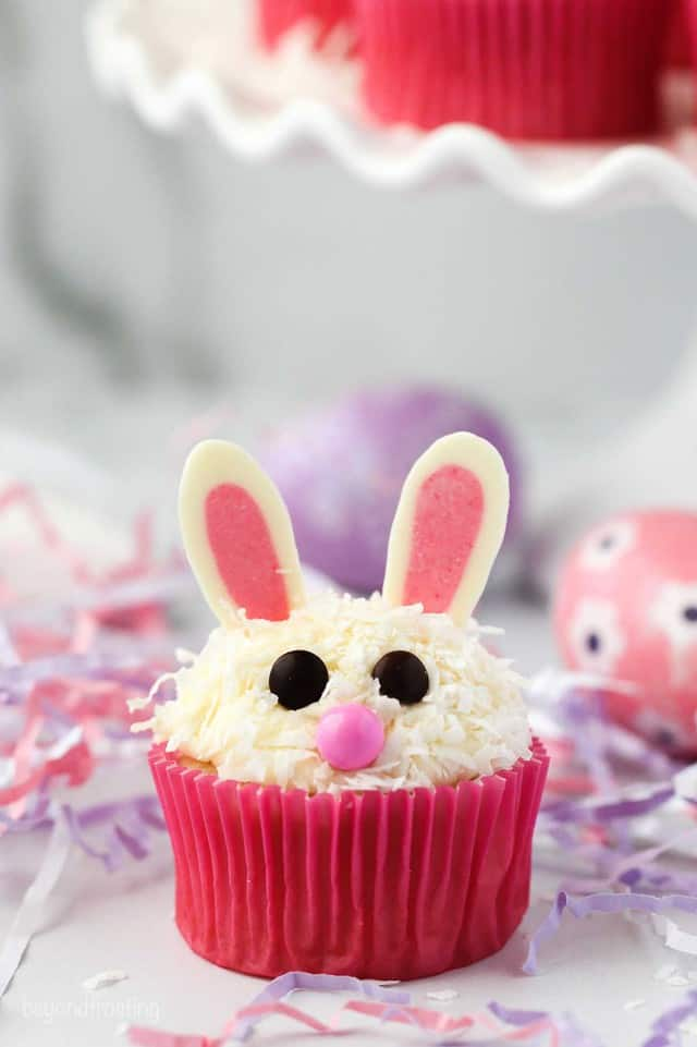 an Easter bunny cupcake sitting in some pink and purple Easter grass