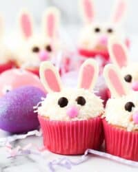 cupcakes decorated like bunnies with pink wrappers