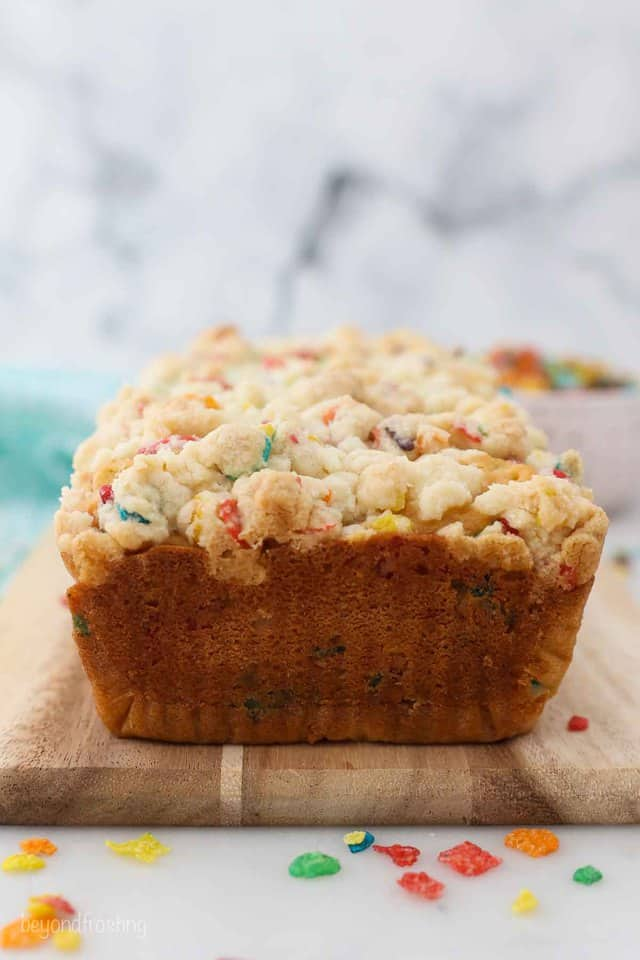 A loaf of Fruity Pebble Cake on a cutting board