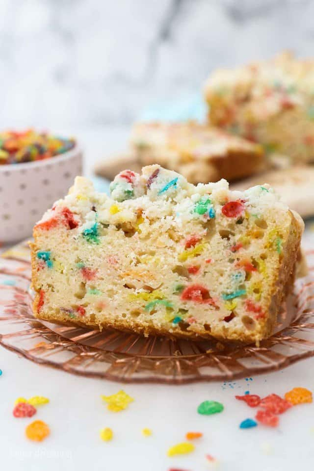 two slices of Fruity Pebble pound cake on a pink glass plate