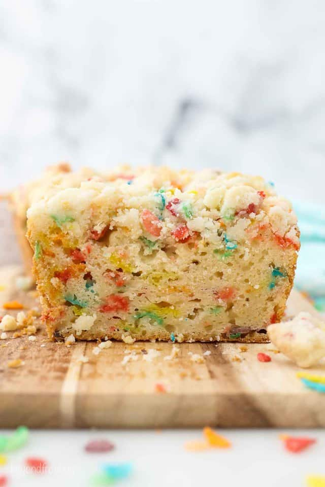 a sliced loaf of Fruity Pebble pound cake showing the inside of the cake