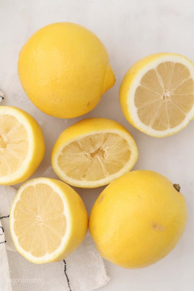 Two Whole Lemons Next to Two Halved Lemons on a White Countertop