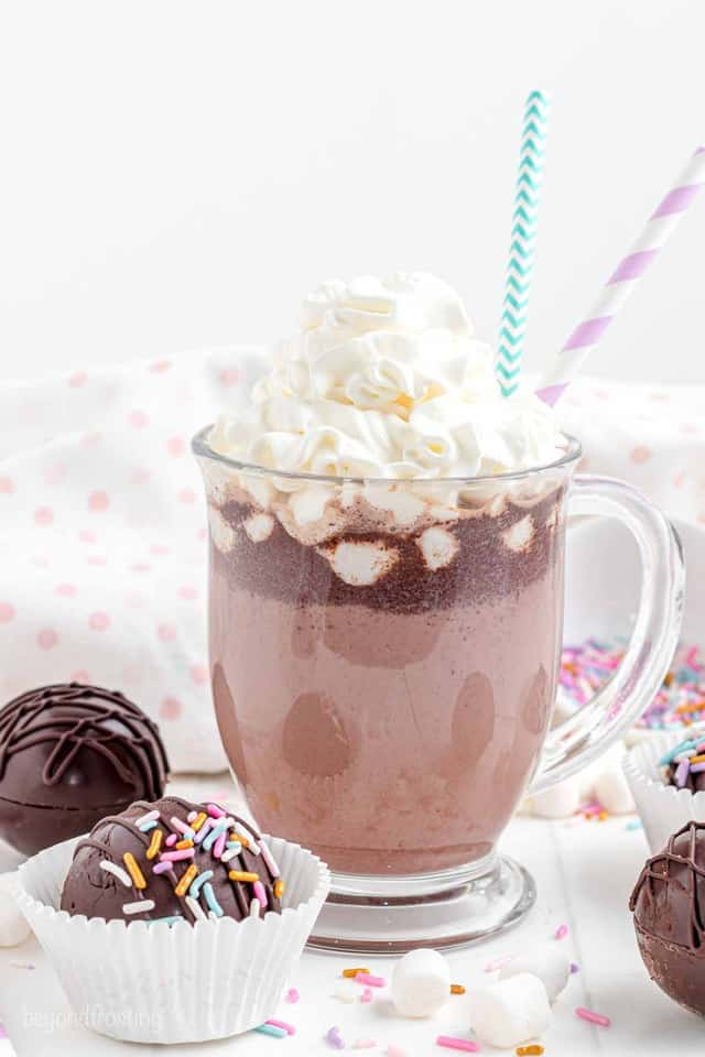 A glass mug with hot chocolate and whipped cream with two paper straws