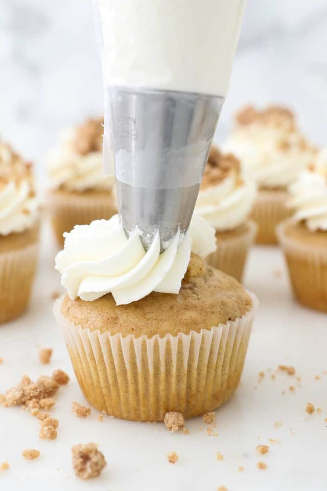 A piping bag frosting a cupcake