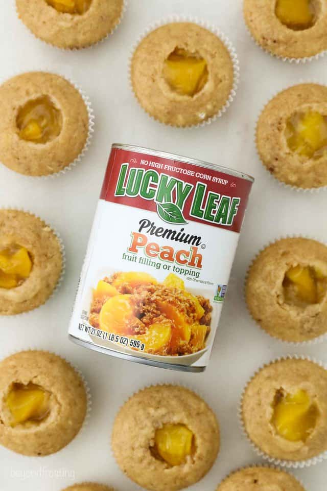 a can of Lucky Leaf Peach pie filling sitting amongst some peach filled cupcakes