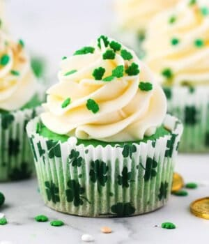 A green colored cupcake frosted and decorated with shamrock sprinkles