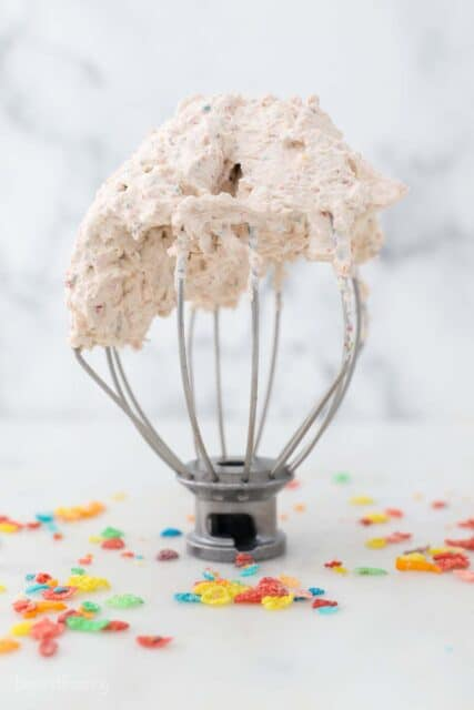 a wire whisk with whipped cream surrounded by Fruity Pebbles Cereal